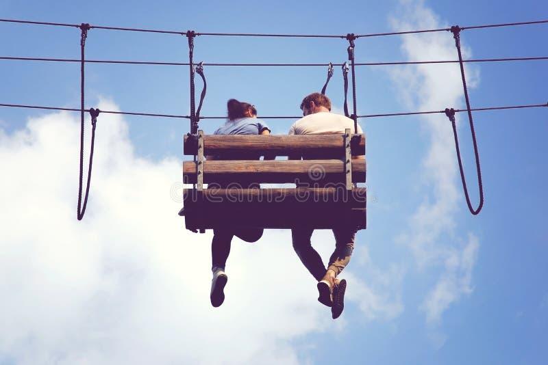Réunion romantique dans les cieux, pieds balançants se reposants de couples sur un banc accrochant images stock