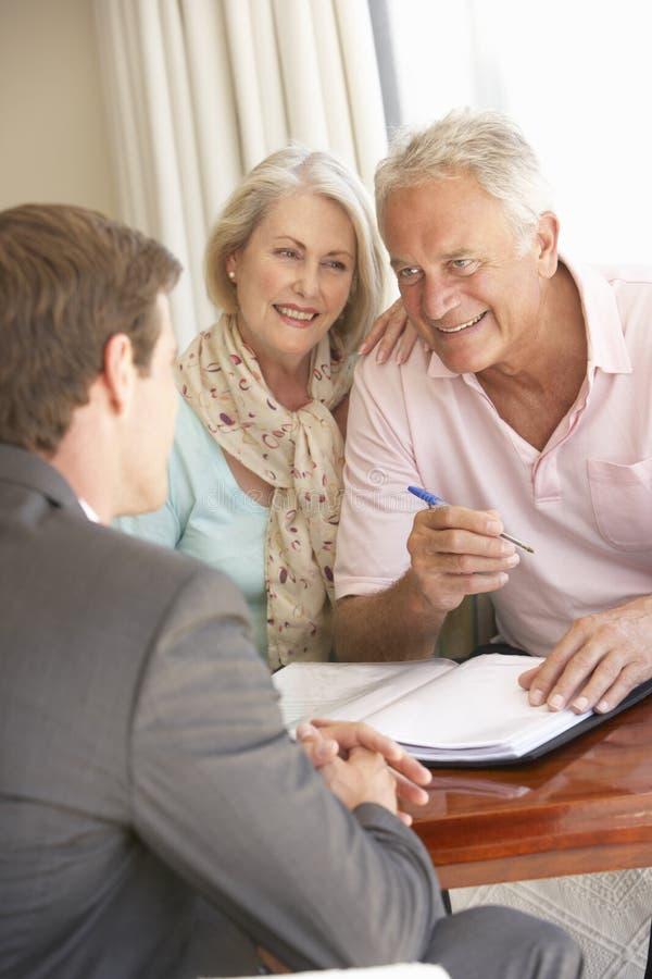 Réunion supérieure de couples avec le conseiller financier à la maison images stock