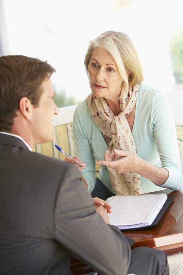 Réunion supérieure de femme avec le conseiller financier à la maison images stock