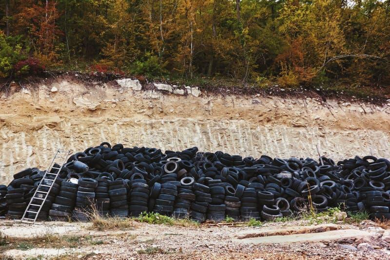 Réutilisation de pneu en caoutchouc la vieille voiture d'occasion fatigue à un entrepôt de ferraille dans les piles attendant réu images stock