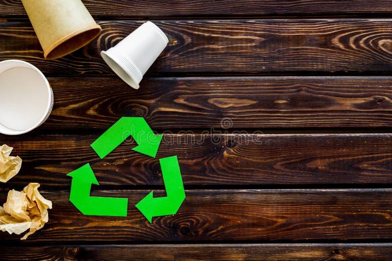 Réutilisation du symbole avec le papier et la tasse en plastique pour l'écologie sur le copyspace en bois de vue supérieure de fo images libres de droits