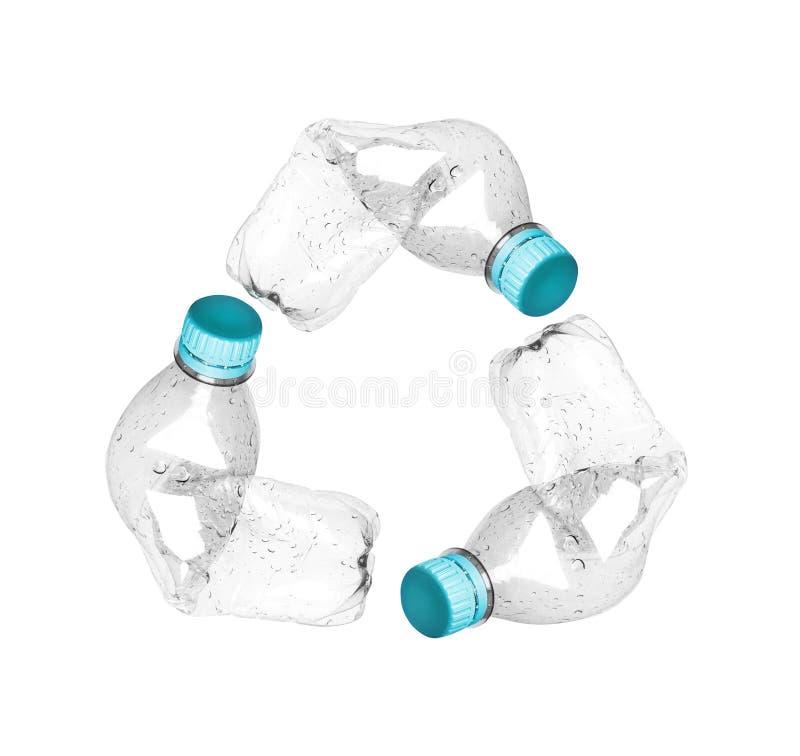 Réutilisez le symbole fait de bouteilles en plastique chiffonnées d'isolement sur le fond blanc photographie stock