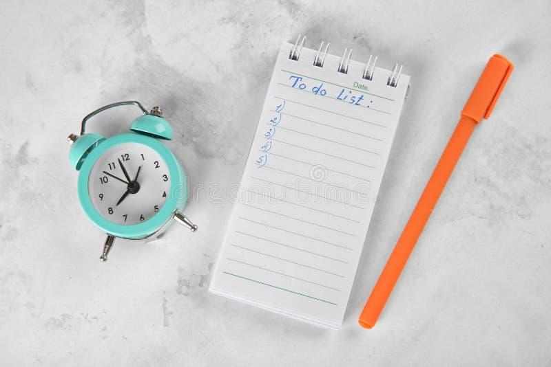 Réveil avec la liste de stylo et de remue-ménage sur le fond clair Concept de gestion du temps photos libres de droits