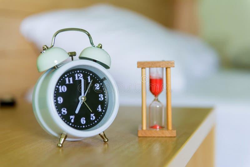 réveil avec le sablier sur le lit dans la chambre à coucher photographie stock