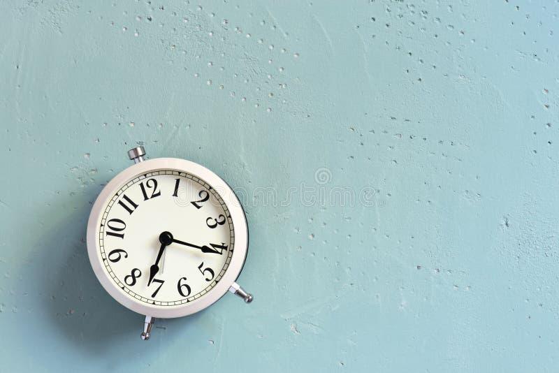 Réveil blanc sur la table texturisée bleue photo libre de droits