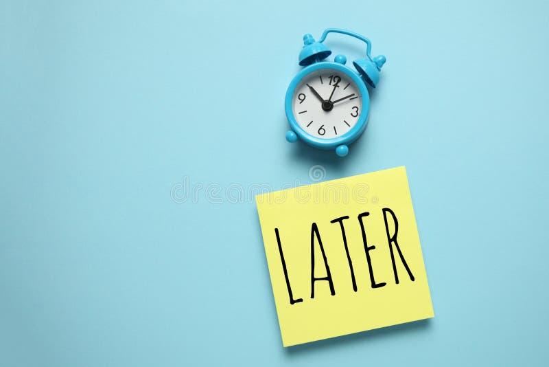 Réveil bleu et rappel papier, plus tard Gestion du temps, priorités, efficacité, contrôle et objectifs photos stock