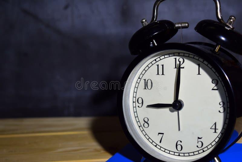 Réveil de noir de fond de vintage de concept rétro sur 21 12h ou 09 0h du matin et livre bleu photo libre de droits