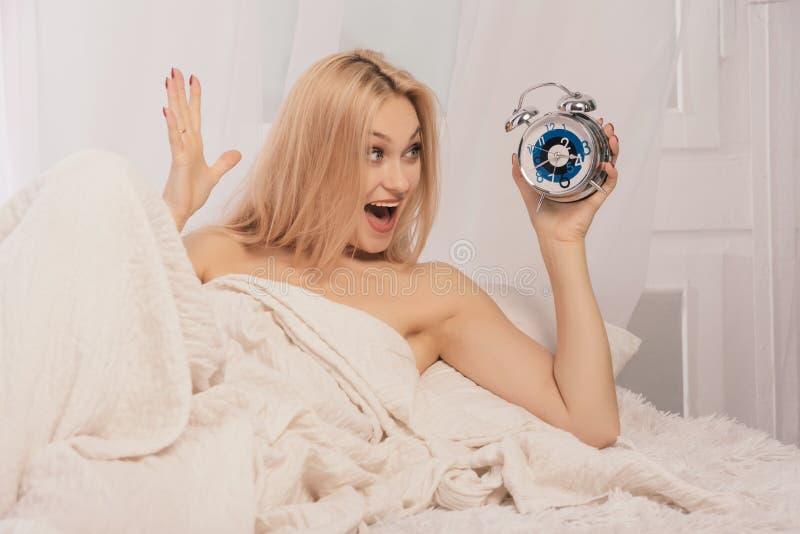 Réveil effrayé de participation de femme sur le lit à la maison photo stock