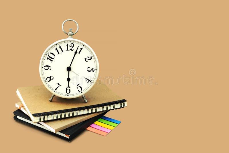 Réveil empilé sur le carnet brun et noir avec un papier de note de post-it D'isolement sur le fond brun avec l'espace et l'agrafe photo libre de droits
