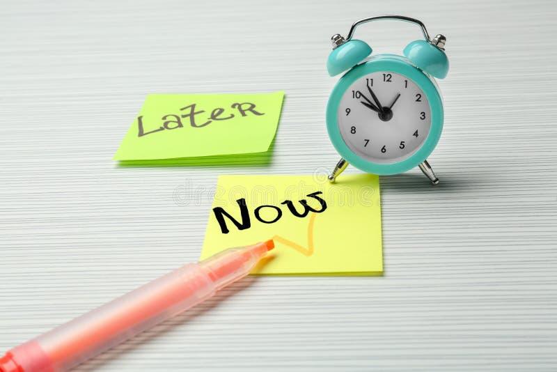 Réveil et feuilles de papier pour des notes sur la table Concept de gestion du temps photos stock