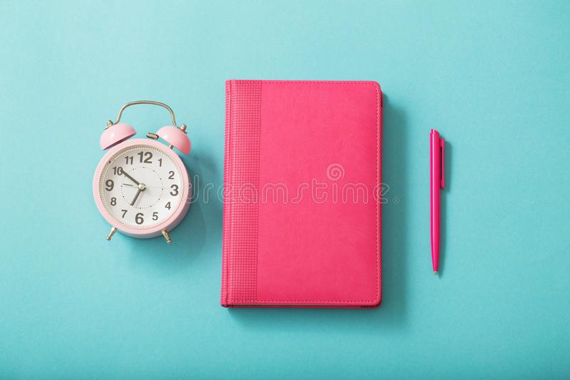 Réveil et journal intime sur le fond de papier en pastel photos stock