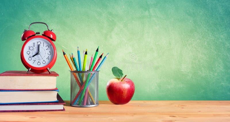 Réveil et pile de livres avec les crayons et l'Apple photos libres de droits