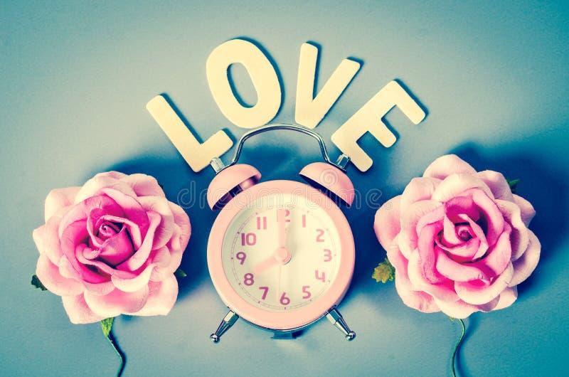 Réveil et rose roses de rose avec le mot d'amour photos libres de droits