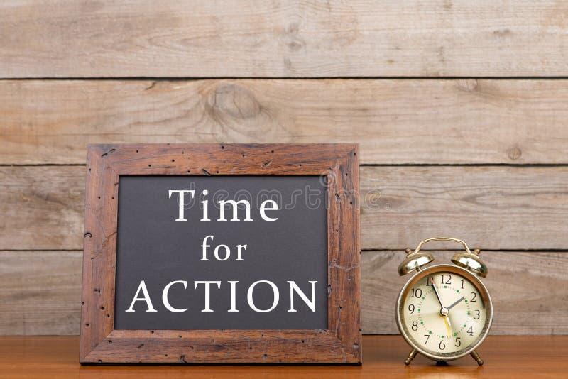 """Réveil et tableau noir avec le texte """"heure pour l'action """" photos libres de droits"""
