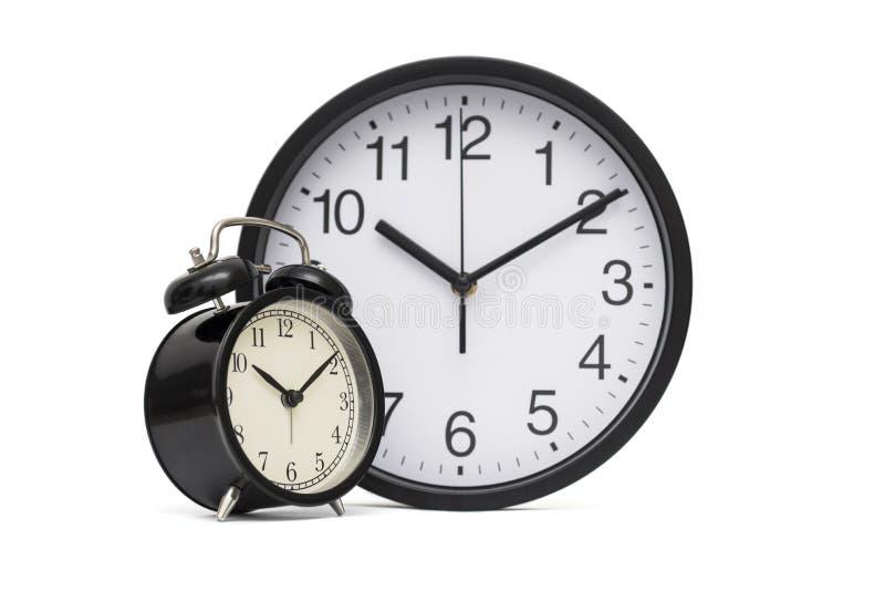 Réveil noir de cru sur le fond des heures de bureau modernes Réveil et horloge noirs de bureau sur un fond blanc photos stock