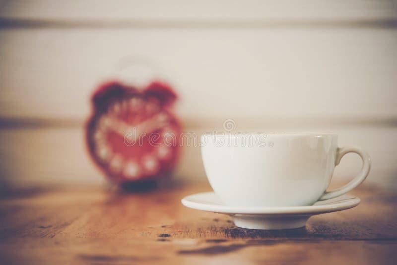 Réveil rouge avec du café sur la table en bois Temps de pause-café photos stock