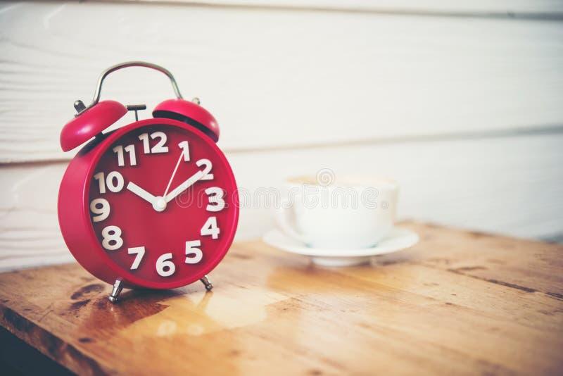 Réveil rouge avec du café sur la table en bois Temps de pause-café photographie stock libre de droits