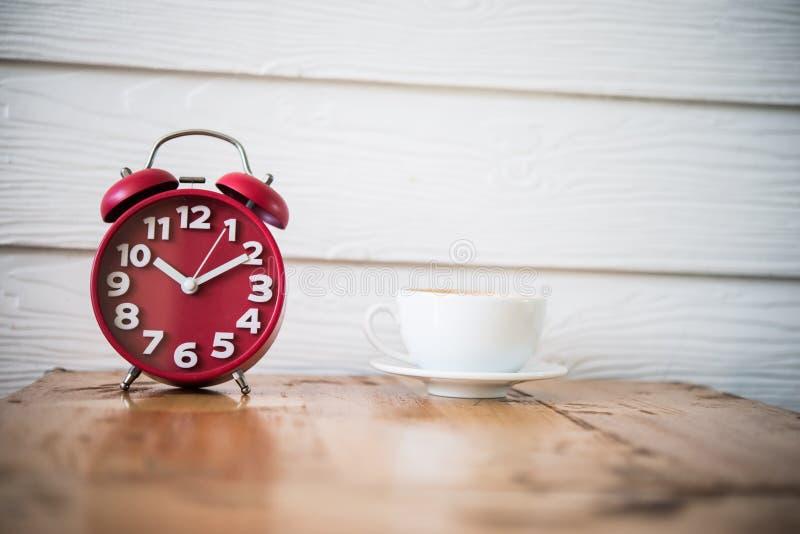 Réveil rouge avec du café sur la table en bois Temps de pause-café photos libres de droits