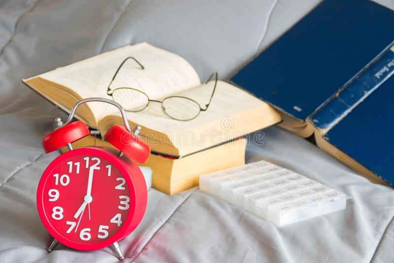 Réveil rouge avec le livre ouvert sur la boîte de strack et de pilules photos libres de droits