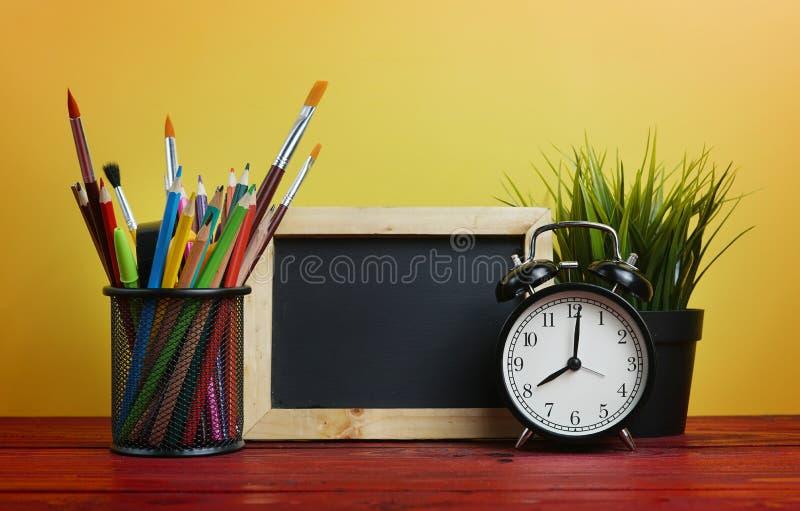 Réveil, tableau noir, usine et école stationnaires dans le panier o photographie stock