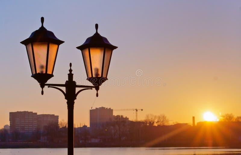 Réverbère à l'aube, éclairage routier dans le coucher du soleil photos stock