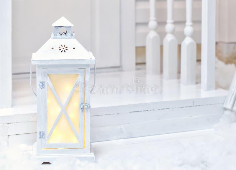 Réverbère blanc de grand vintage se tenant sur le porche avec la neige image stock