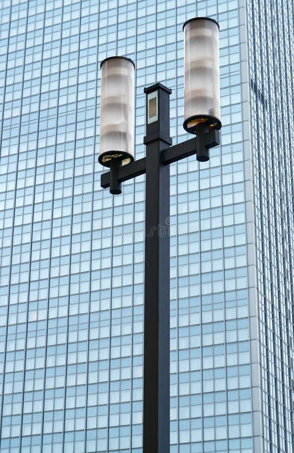 Réverbère contre la façade d'un gratte-ciel moderne images stock