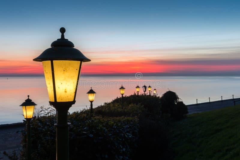 Réverbères le long de boulevard néerlandais avec le beau coucher du soleil au-dessus de la mer photos stock