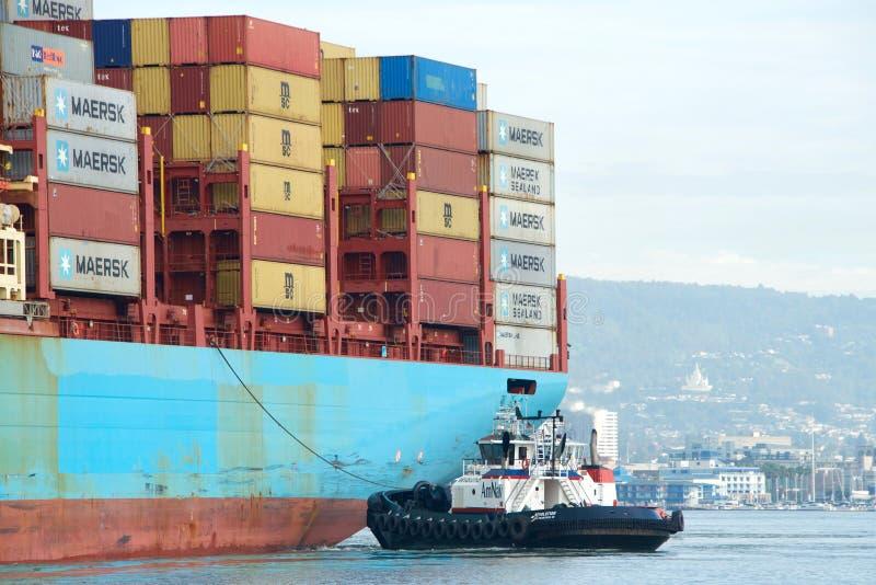 RÉVOLUTION de remorqueur aidant la manoeuvre de GERD MAERSK de cargo photographie stock