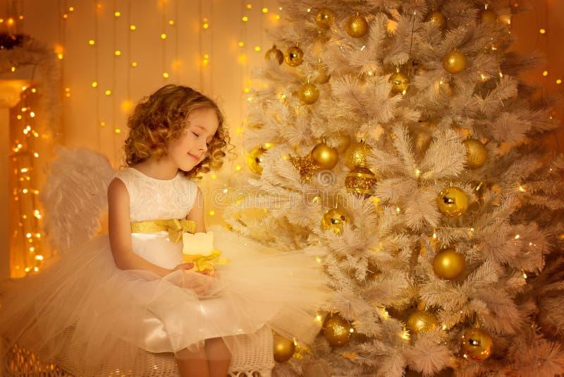 Rêve d'enfant sous l'arbre de Noël, fille heureuse avec la bougie photos libres de droits