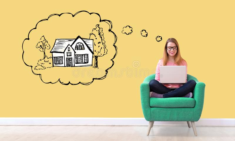 Rêver de la nouvelle maison avec la femme à l'aide d'un ordinateur portable image stock