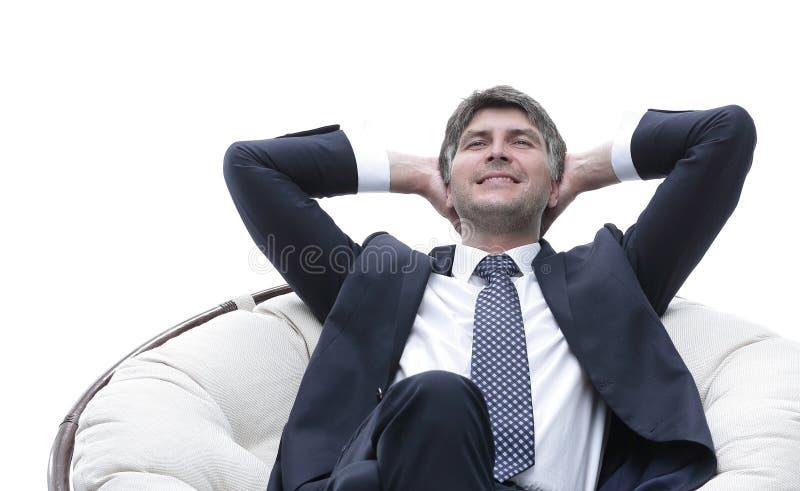 Rêver l'homme d'affaires est repos, se reposant dans une grande chaise molle photos stock