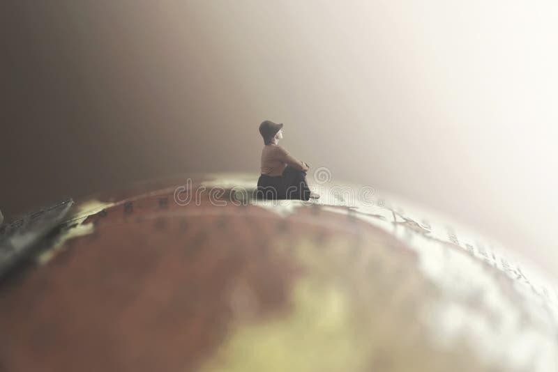 Rêver la femme regarde la séance infinie sur un globe géant photo libre de droits