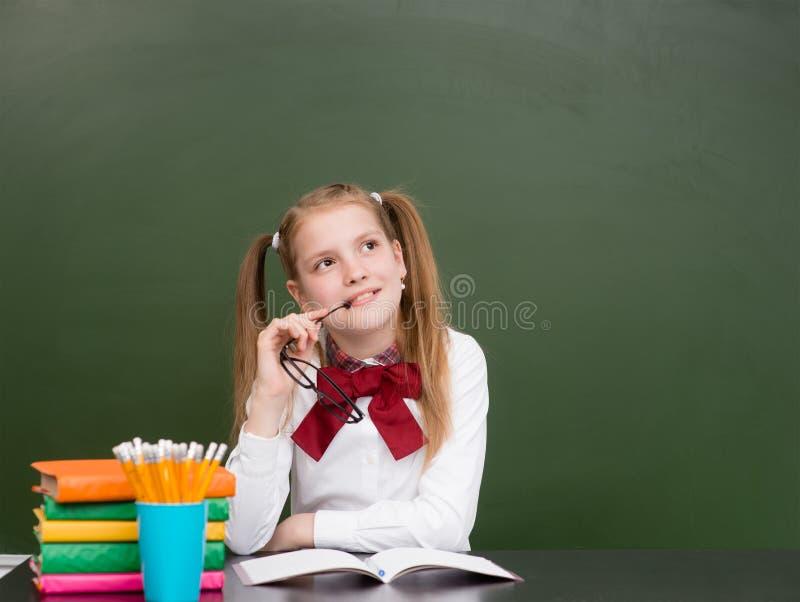 Rêver la fille de l'adolescence près du tableau vert d'école vide photo libre de droits