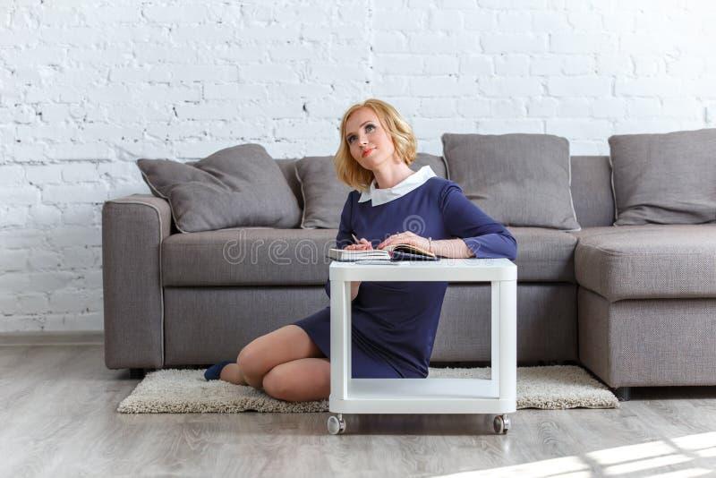 Rêver la jeune femme s'asseyant à la table avec son carnet photographie stock libre de droits