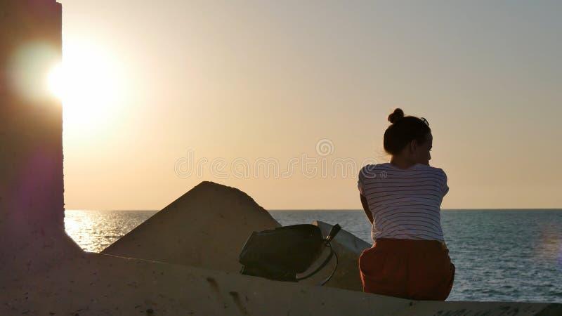 Rêver la jeune femme s'asseyant sur les roches près de la mer au coucher du soleil photos stock