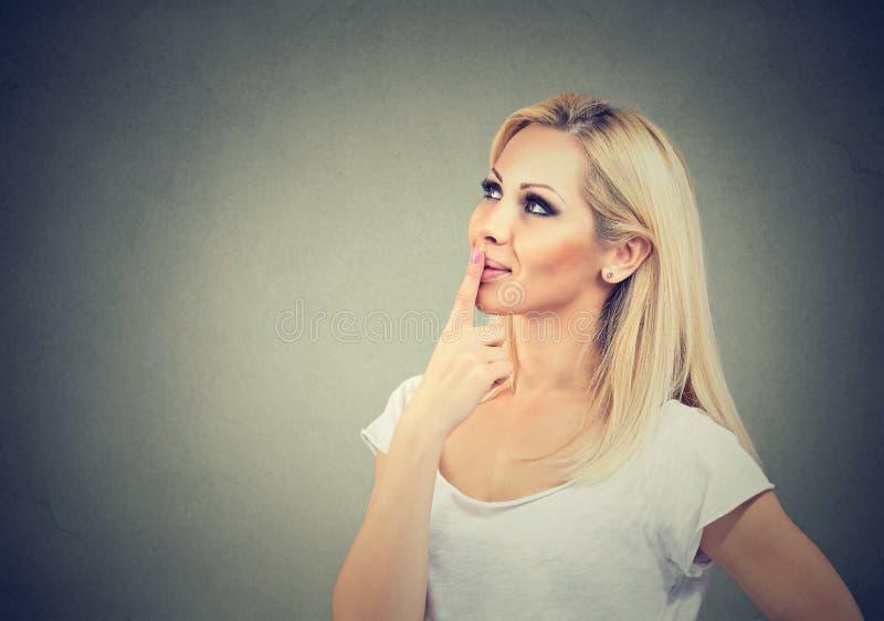 Rêver les lèvres émouvantes de femme sur le gris photographie stock libre de droits