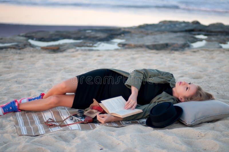 Rêver menteur de belle femme sur la plage en automne image libre de droits