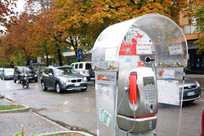 Rímini, Italia - noviembre de 2011: Una caja de llamada con el receptor rojo en la calle por el camino imagen de archivo libre de regalías