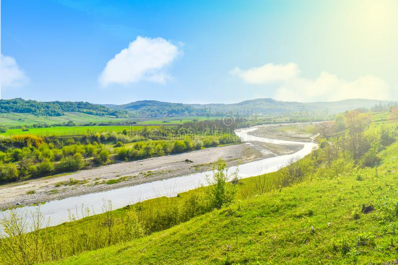 Río brillante brillante en el valle verde con la hierba verde y el cielo azul en un día soleado del verano Paisaje del verano en  fotos de archivo