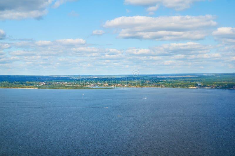 Río contra el cielo azul con las nubes y el bosque imagen de archivo