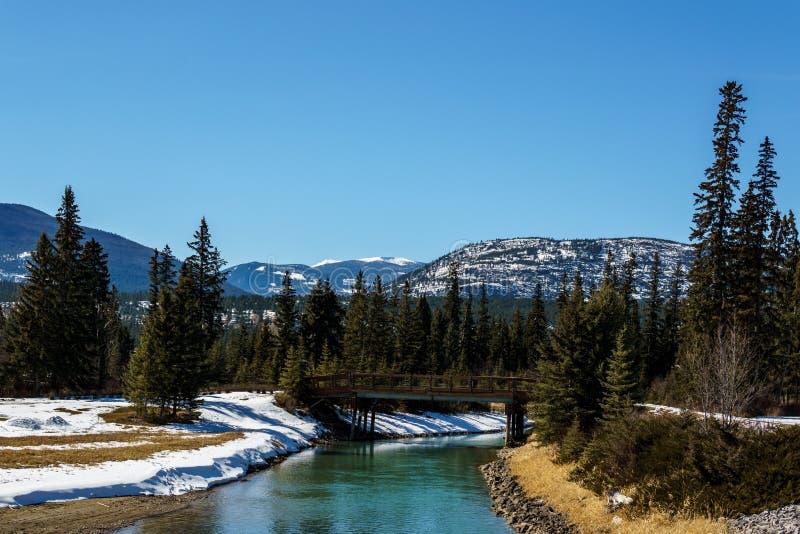 Río de la montaña con el puente de madera en la Columbia Británica del este Canadá de la primavera temprana imágenes de archivo libres de regalías