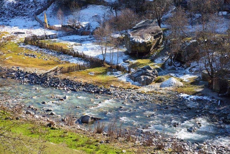 Río de la montaña que atraviesa el pueblo de Mestia en día soleado frío en último otoño imágenes de archivo libres de regalías