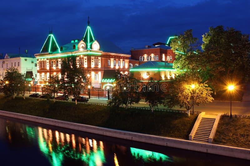 Río de la noche con el edificio de la ciudad provincial de las iluminaciones imagenes de archivo