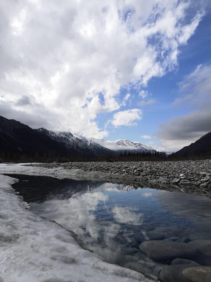 Río de la primavera en el cielo azul de la nieve de las montañas fotos de archivo libres de regalías