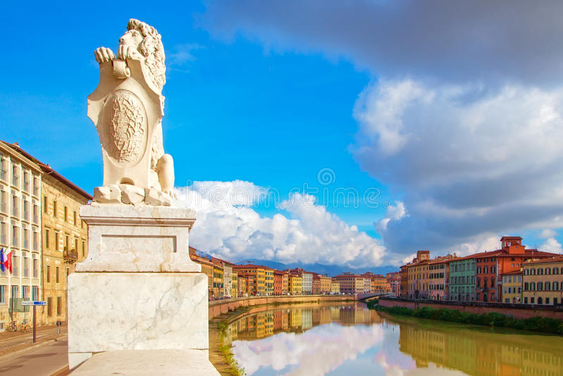 Río de Pisa, de Arno, estatua del león y reflexión de los edificios Lungarno fotografía de archivo