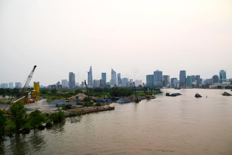 Río de Saigon y emplazamiento de la obra delante del horizonte de Ho Chi Minh City fotos de archivo