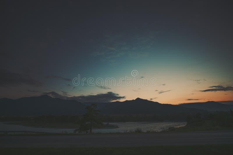 Río del camino de tierra, de Katun y montañas en puesta del sol fotos de archivo