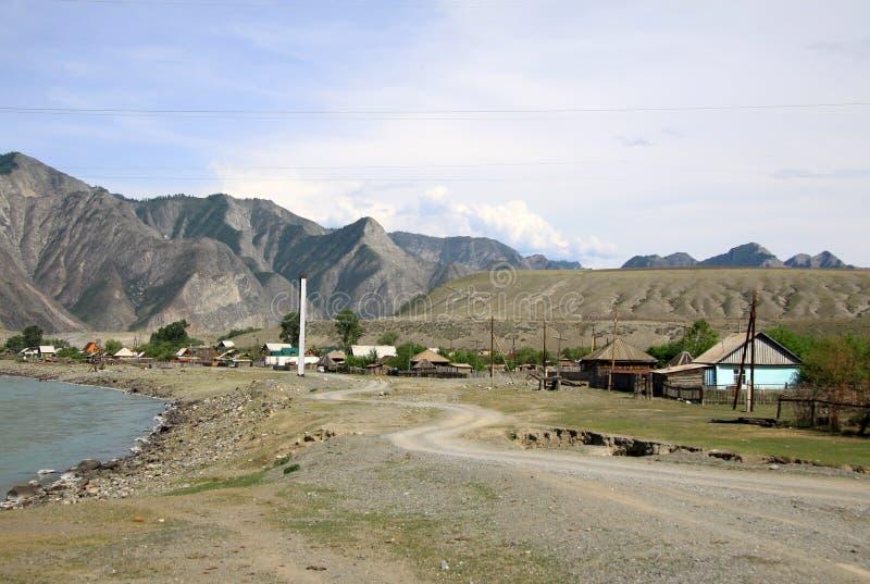 Río Katun de la montaña y un pueblo en las montañas de Altai, Rusia imagenes de archivo