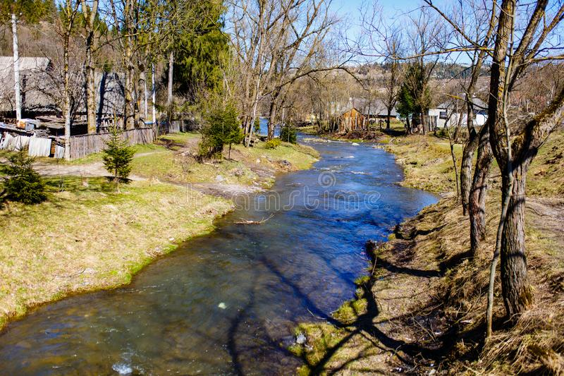 Río montañoso que atraviesa el pequeño pueblo Resorte temprano fotografía de archivo